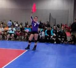 Volleyball line judge signaling ball hit the antenna